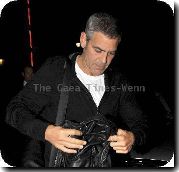 George Clooney in blue jeans, heavy boots and a black leather jacket arrives at his hotel.