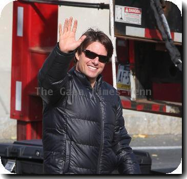 Tom Cruise in a black puffa jacket waves to fans during filming on the set of his new movie 'Wichita' Boston.