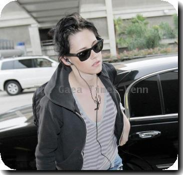 Kristen Stewart  listening to her iPod as she arrives at LAX airport to catch an Alaska Airlines flight. Los Angeles, California.