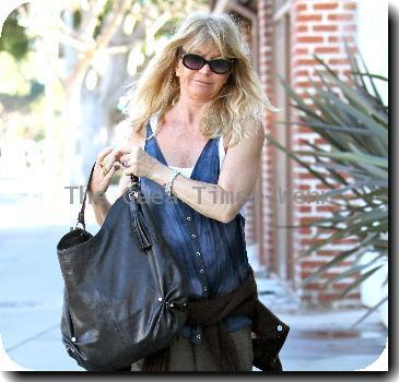 Goldie Hawn wearing baggy trousers and an oversized waistcoat together with a cardigan tied around her waist, pays a parking meter with a credit card on her way to a pharmacy in Santa Monica..