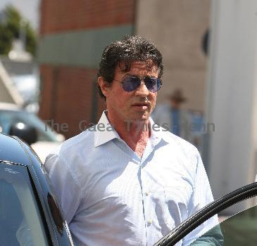 Sylvester Stallone  signs an autograph for a fan while out and about in Beverly Hills smoking a cigar. Los Angeles, California, USA.