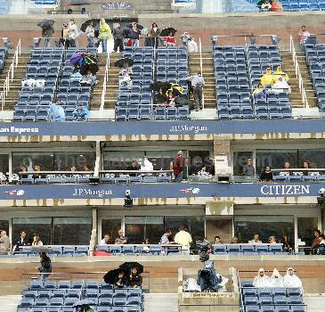 Fans brave the rain at the USTA Arthur Ashe Stadium in Flushing, Queens. The US Open men's tennis final championship match between top-seeded Rafael Nadal and third-seeded Novak Djokovic has been rescheduled at 4 p.m. on Monday, 13 September, because of rain. New York City, USA.